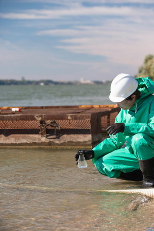 environmentalist: Environmentalist with sample of water collected close to the drainage hose Stock Photo