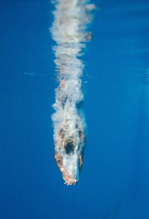 Female diver enters the water of a swimming pool