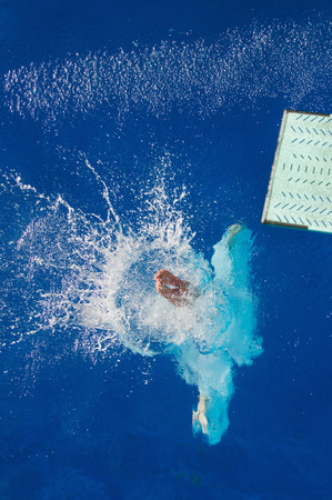 springboard: Water splashes as springboard diver breaks the surface. Foto de archivo