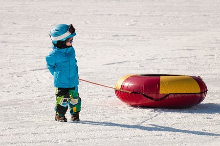 Cute little boy preparing for snow tubing downhill