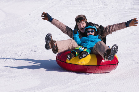 Young woman and little boy snowtubing