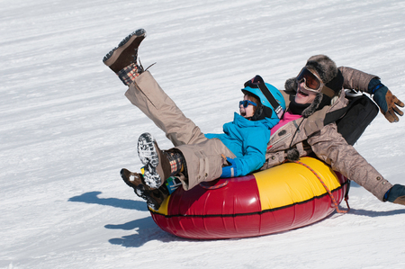 Mother and son snow tubing down the hill