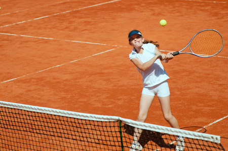 one person only: Young girl on tennis court hitting the ball with backhand slice Stock Photo