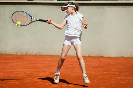 forehand: Young girl hitting the ball with forehand slice on clay court Stock Photo
