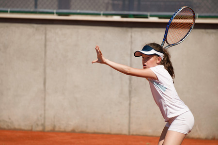 forehand: Junior female tennis player on clay court practicing forehand