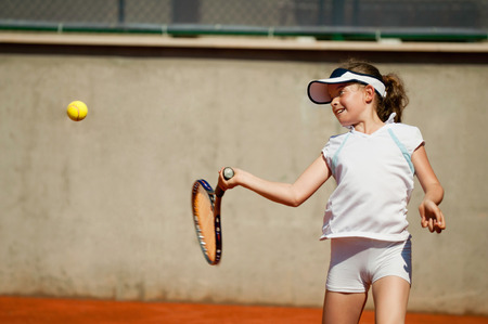 forehand: Young girl practicing forehand on clay court