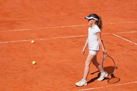 pursuits: Young girl during tennis trainning on a clay