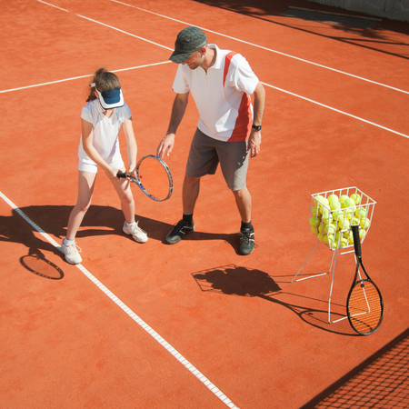 talented: Tennis coach instructing young talented girl Stock Photo