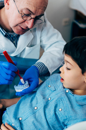 anatomical model: Dentist with little boy, talking about dental hygiene Stock Photo