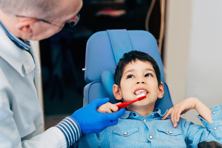 males only: Dentist with little boy, talking about dental hygiene Stock Photo