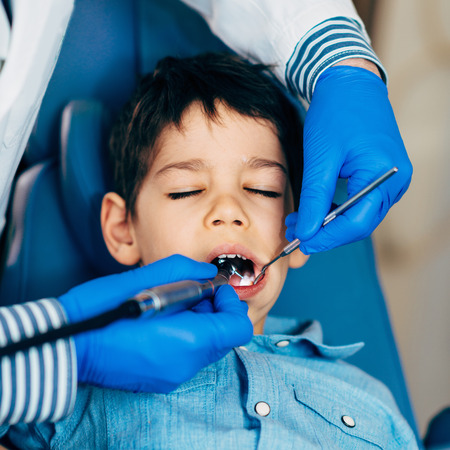males only: Dentist drilling little boys tooth Stock Photo