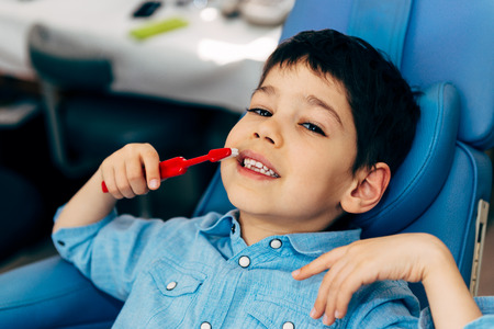 males only: Little boy brushing teeth at dentist office Stock Photo