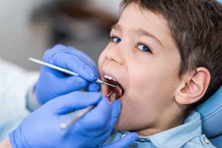 males only: Dentist doing regular dental check-up to little boy. Stock Photo