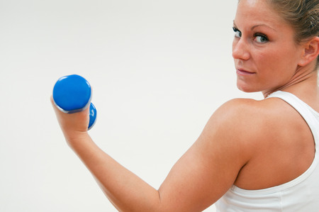 hand weight: Female athlete strengthening her biceps with hand weight Stock Photo