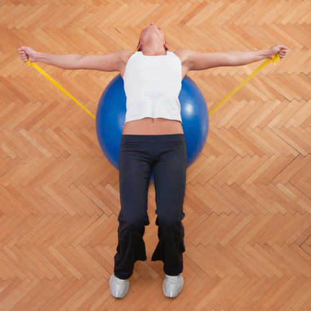 elastic band: Athlete exercising for balance and strenght with elastic band and fitness ball Stock Photo
