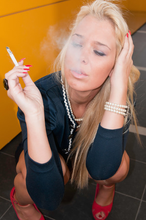 stressed out: Stressed out young woman intensively smoking. Stock Photo