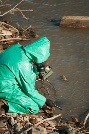 environmental damage: Technician looking for traces of radiation in the water