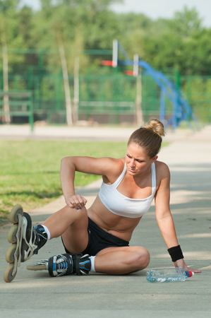 attractive female: Attractive female with roller skates after falling Stock Photo