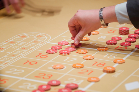 roulette player: Roulette player placing chips on the table Stock Photo