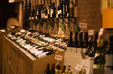 wine store: Wine store & cellar. Focus set on the bottles in the main rack. Stock Photo