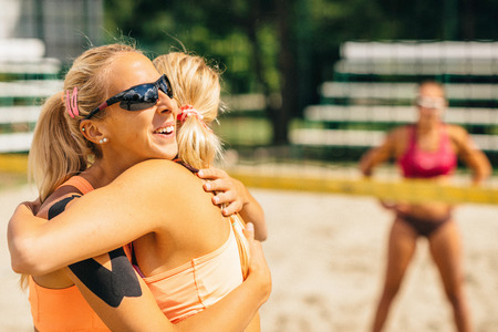 succesful: Beach volleyball girls hugging after a succesful game point