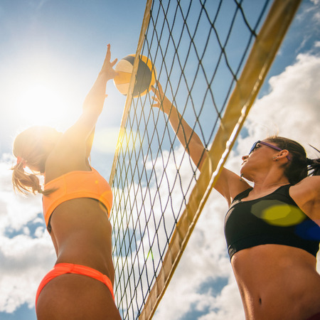 Beach volleyball girls clashing at the net, defender blocking the spike