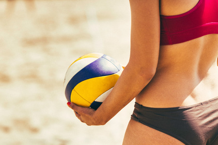 four person only: Female beach volleyball player standing with ball, ready to serve Stock Photo