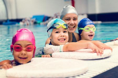 Bambini con istruttore di nuoto, divertirsi sul bordo piscina