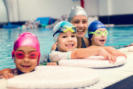 Kids with swimming instructor, having fun on the pool edge Stock Photo