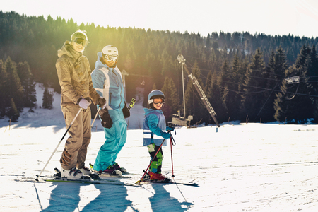 Skiing family - enjoying sunshine on the mountain ski slope. Toned imafe