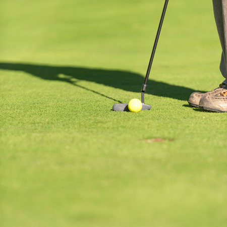 putter: Putting shot. Golf ball and putter in focus, blurred hole and shadow of a golfer. Lots of copy space