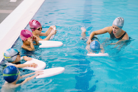 5 6 years: Group swimming lesson for children - swimming instructor working with one child, other kids watching. 5 to 6 years old children, indoor pool.