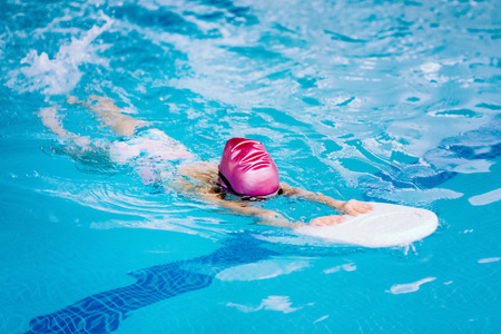 Little girl swimming with kicking board
