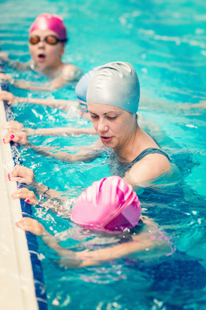 breathing exercise: Breathing exercise at swimming class for children - Kids practicing breathing with swimming instructor. Stock Photo