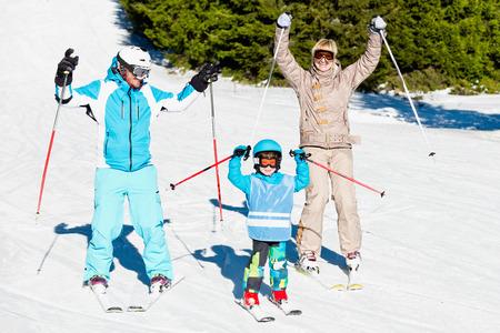 Cheerful family skiing - enjoying sunshine on the mountain