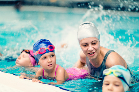 Swim school - Swimming instructor with group of children