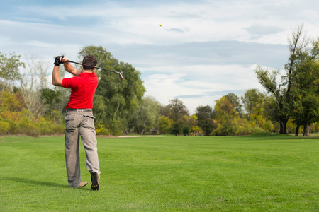 air hole: Golfer playing from fairway on a long hole, golf ball visible in the air