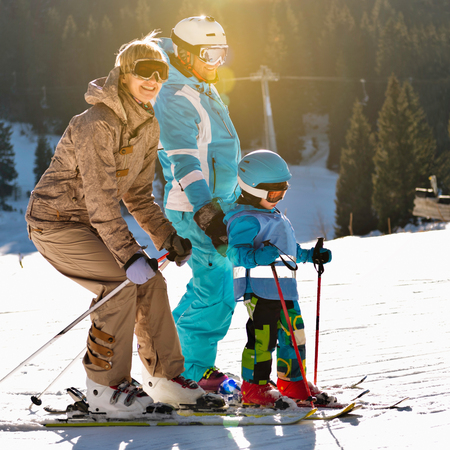 winter vacation: Family on winter vacation - skiing on a sunny day Stock Photo