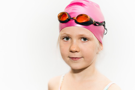 6 year old: Portrait of a cute 6 year old girl with swimming goggles and cap