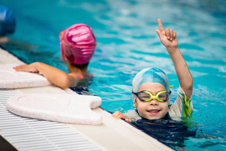 swimming race: Kid who won the swimming race in swimming class for little children