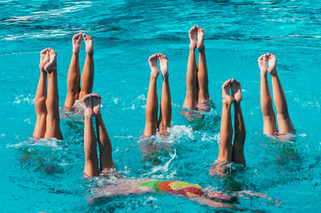 Synchronized swimmers performance with legs outside water 版權商用圖片 - 61042502