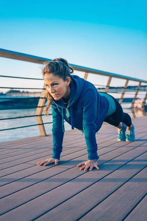 Woman doing plank on riverside