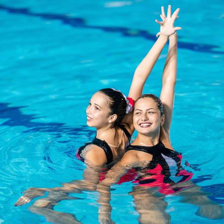 Gesynchroniseerde Zwemmers dansen in het zwembad Stockfoto - 61045672