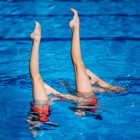 Synchronized swimming duet on performance in the pool