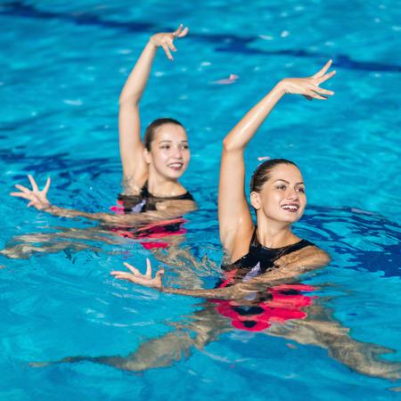 Gesynchroniseerde Zwemmers dansen in het zwembad