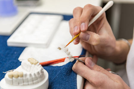 prosthodontics: Dental technician or dentist working with tooth dentures in his laboratory