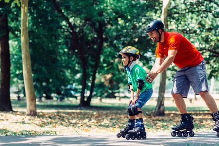 teching: Father teching son roller skating in park Stock Photo