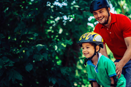 Father teching son roller skating in park Stock Photo