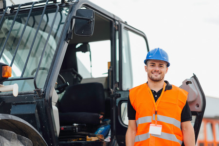 steer: Construction worker with Skid Steer Loader in background Stock Photo