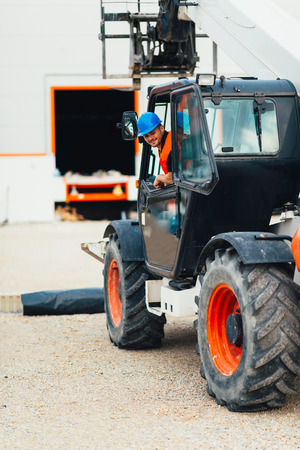 skid loader: Construction worker operating on Skid Steer Loader
